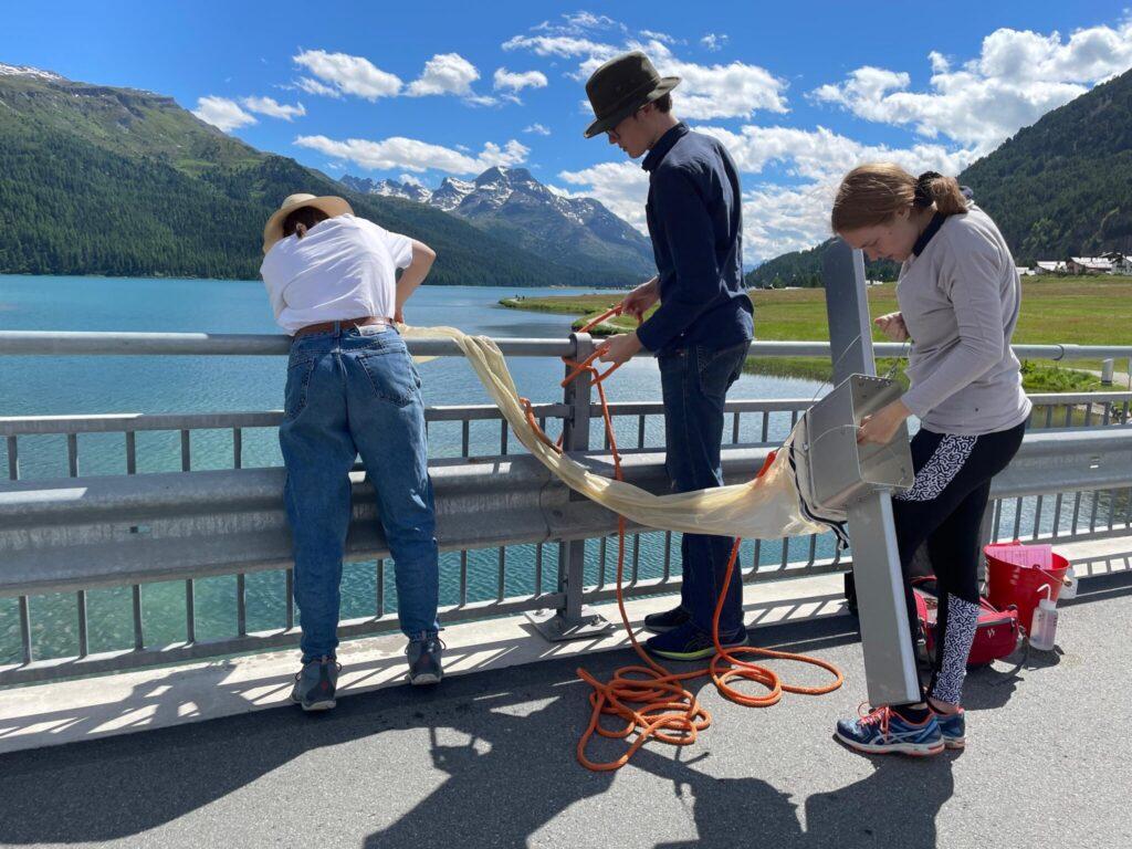 3 Forschende stehen auf einer Brücke und lassen einen Schlauch in das darunterliegende Wasser