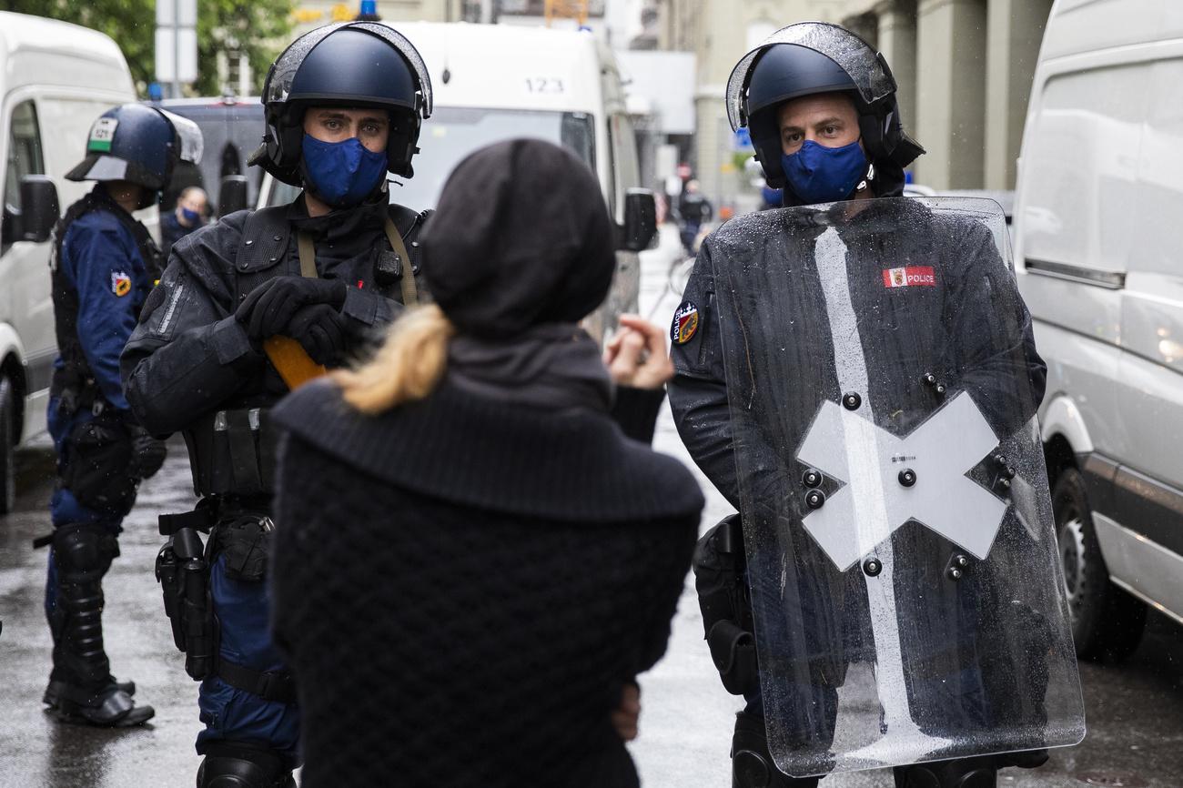 2 Polizisten mit Helmen, Schutzschilden und blauem Mundnasenschutz stellen sich einer Coronamassnahmengegnerin in den Weg.