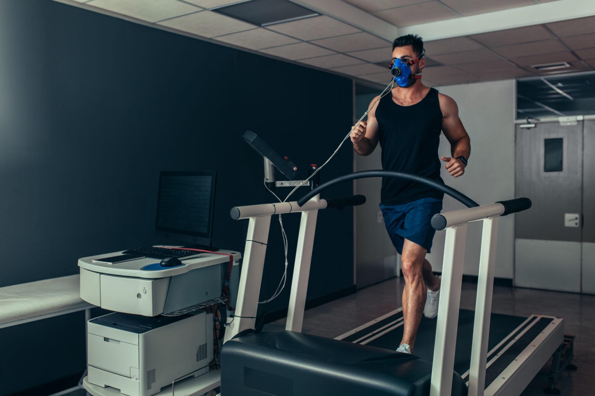 Ein Mann steht mit einer Maske, die den Atem misst auf einem Laufband in einem Sportlabor.